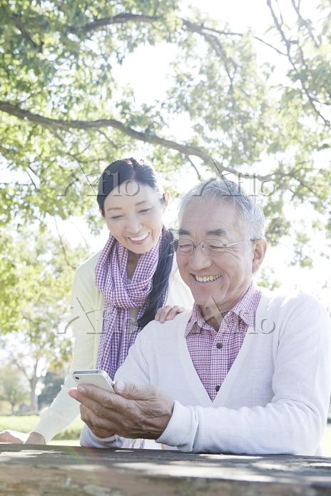 公園でスマートフォンを見るシニア夫婦