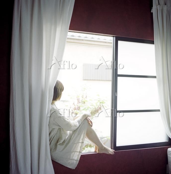窓辺から遠くを見る女性