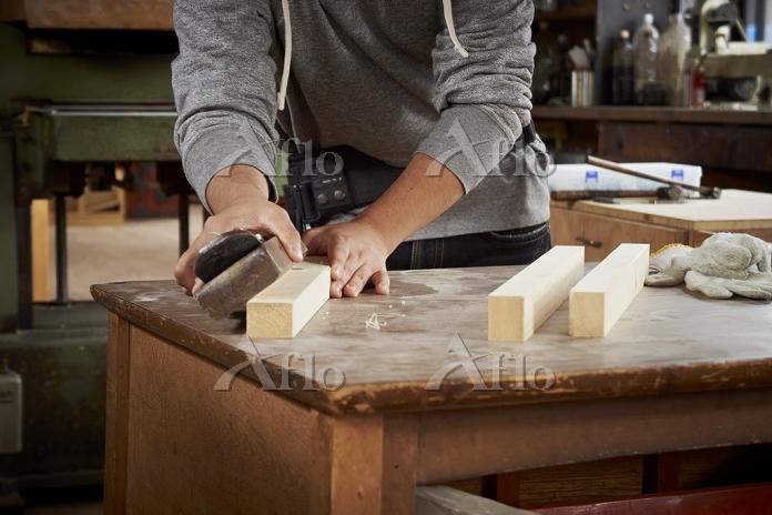 鉋で木材を削る男性