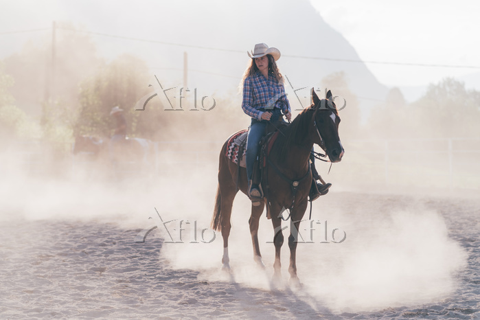 Cowgirl on horse in dusty eque・・・
