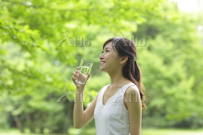 新緑の中で水を飲む若い日本人女性