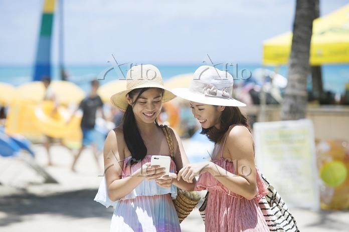 リゾートでスマートフォン検索をする20代日本人女性