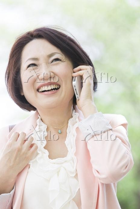 笑顔で電話するミドル日本人女性