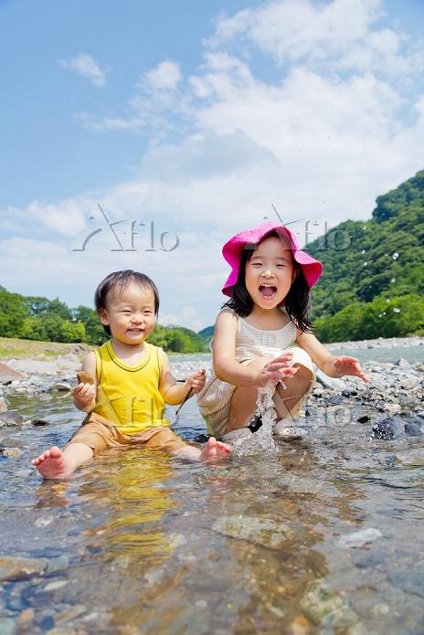 河原で水遊びをする姉と弟