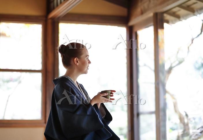 縁側でお茶を飲む女性