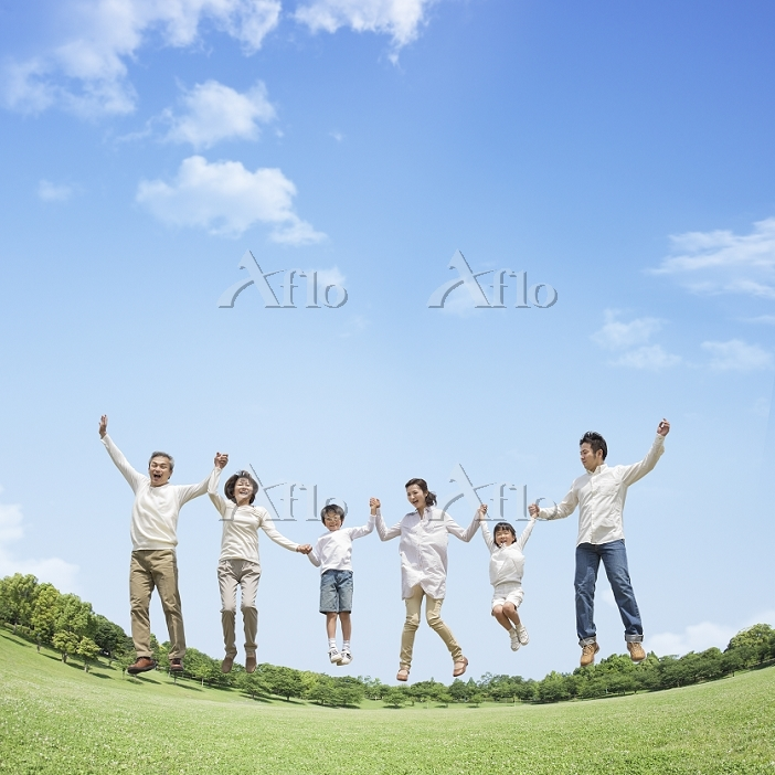 草原でジャンプする日本人の三世代家族