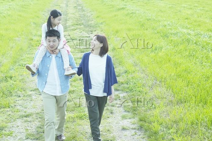 草原を歩く笑顔の日本人家族