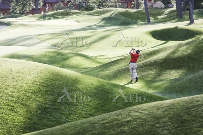フェアウェイからのショットを打つシニアゴルファー