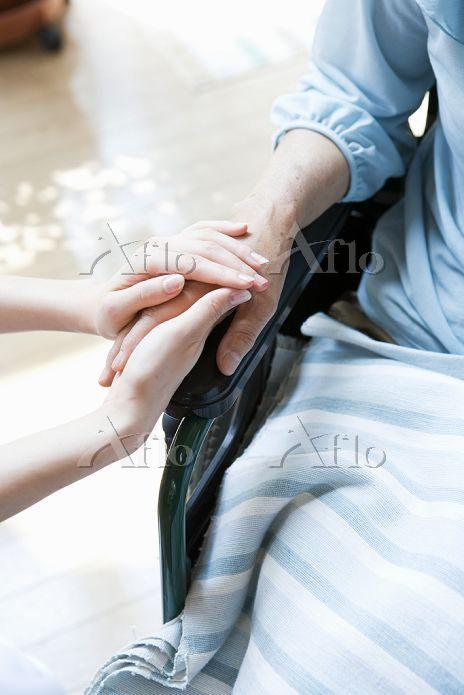 シニアの手を握る介護士