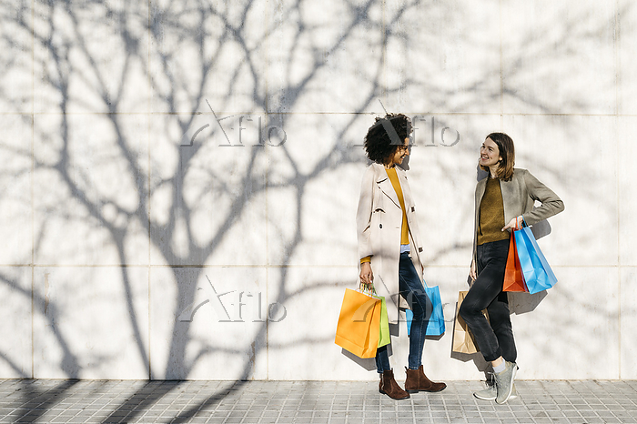 Two happy women with shopping ・・・