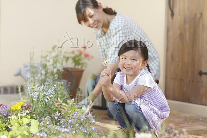 庭でガーデニングをするお母さんと女の子