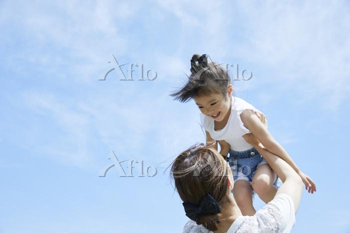 娘を抱き上げる母親
