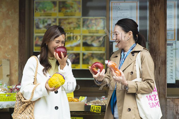 店頭で野菜を選ぶ女性