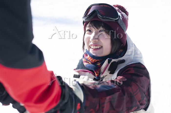 助け起こされるスノーウェアの女性