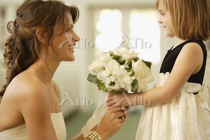 Bride handing bouquet to flowe・・・