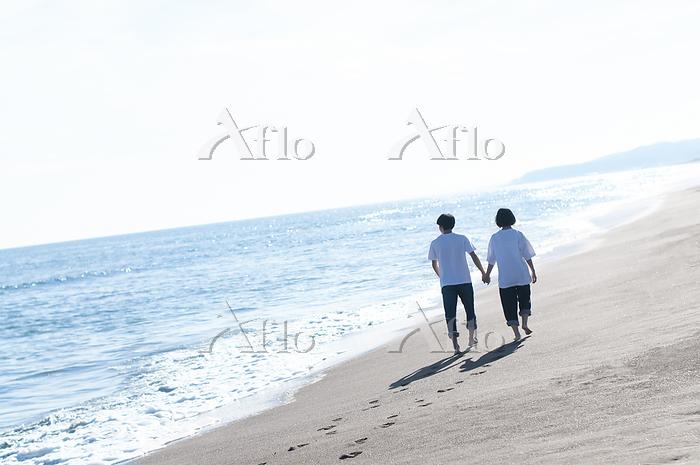 海辺を手をつないで歩くカップルの後ろ姿