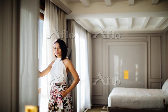 Fashionable woman beside windo・・・