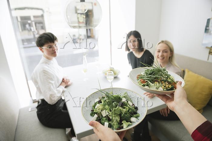 Waiter serving salad to friend・・・