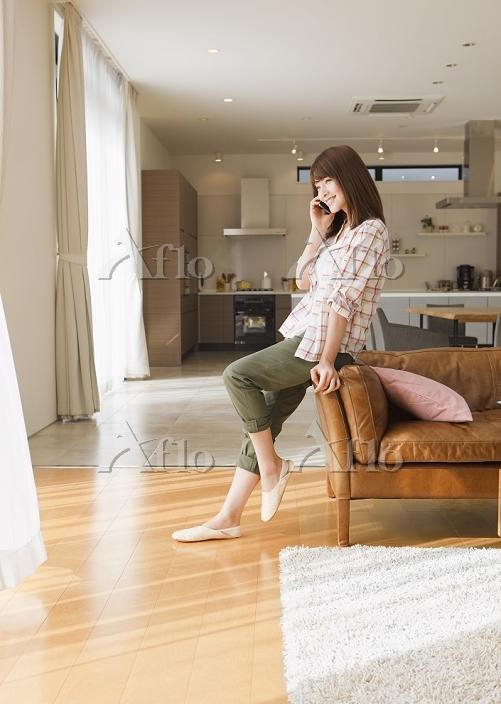 ソファに寄り掛かって通話する日本人女性