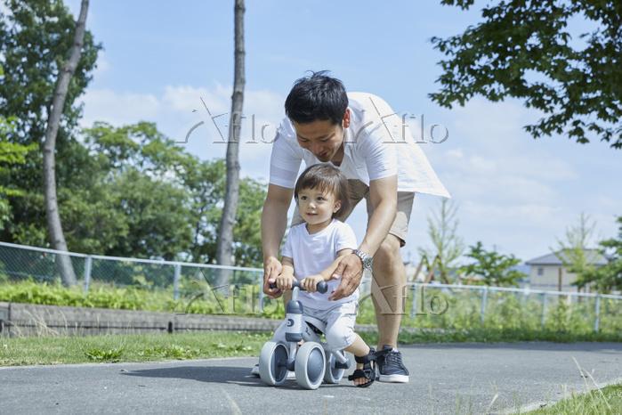 三輪車で遊ぶ日本人親子