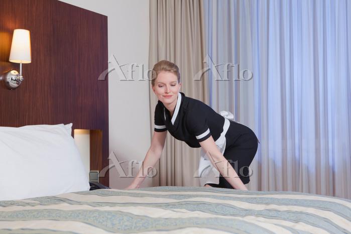 ベッドメイキングをするホテルの従業員