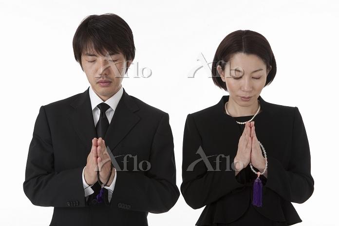 数珠を持ち合掌する喪服姿の夫婦 正面