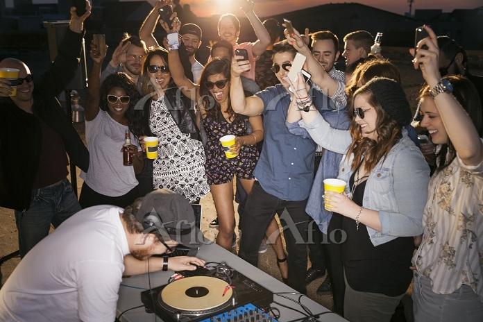 Crowd cheering around DJ at ro・・・
