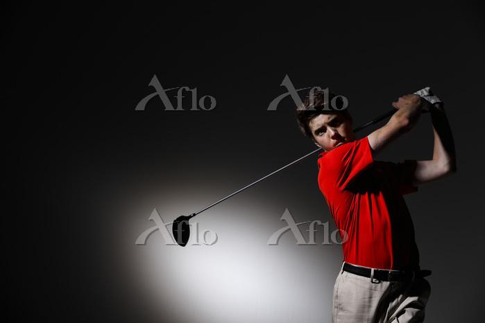 ティーショットを打つ外国人ゴルフ選手