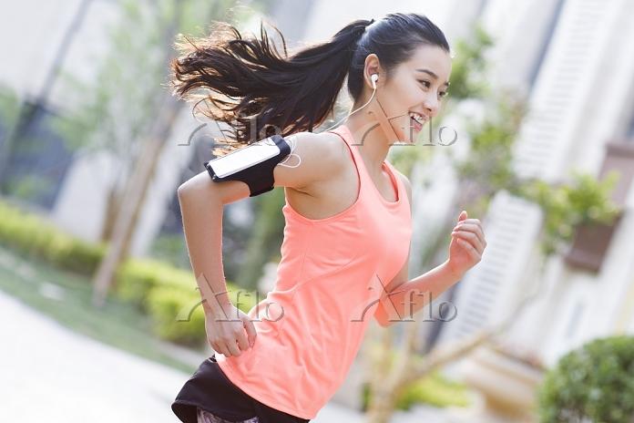 音楽を聴きながらジョギングする女性