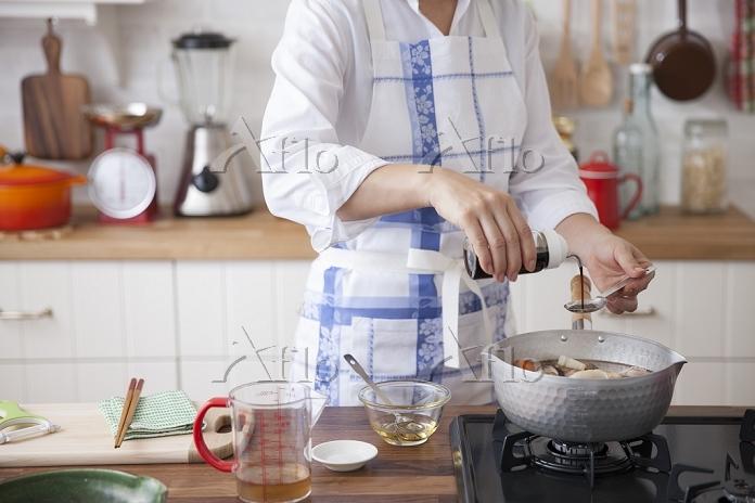 煮物の鍋に調味料を入れる女性