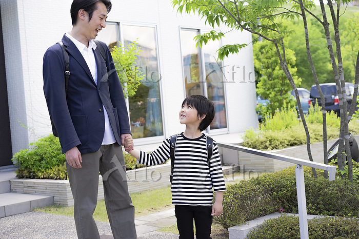 父親と手をつなぐ小学生の男の子