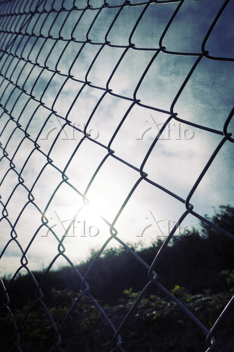 Wire fence against sunrise