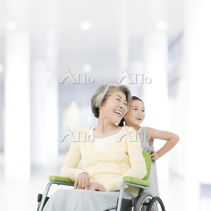 車椅子に乗る祖母を押す孫