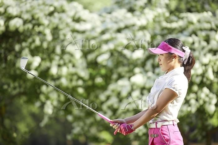 アイアンショットを打つ女子ゴルフ選手