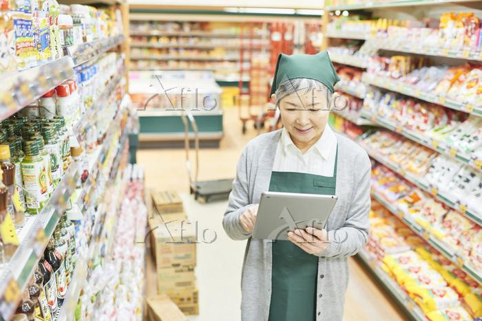 スーパーの在庫を確認するシニア日本人女性