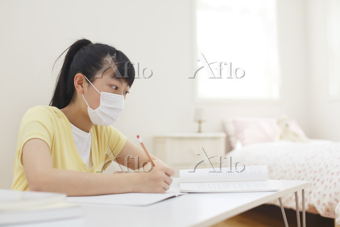 マスクをして授業中をうける女の子