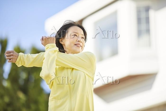 庭で運動をする日本人シニア女性