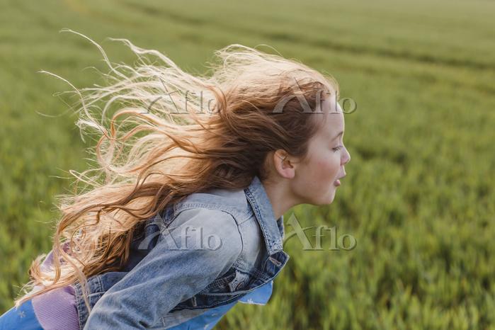風で髪がなびく白人の子供