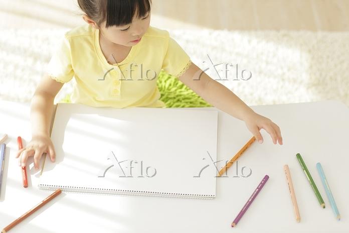 白紙の画用紙に描こうとする女の子