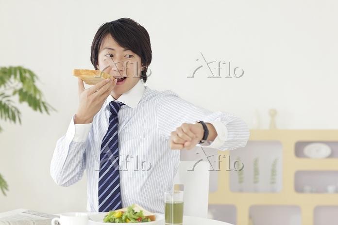 朝食を食べながら時計を見て慌てる日本人ビジネスマン