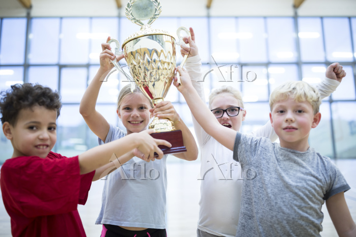 Happy pupils holding trophy in・・・