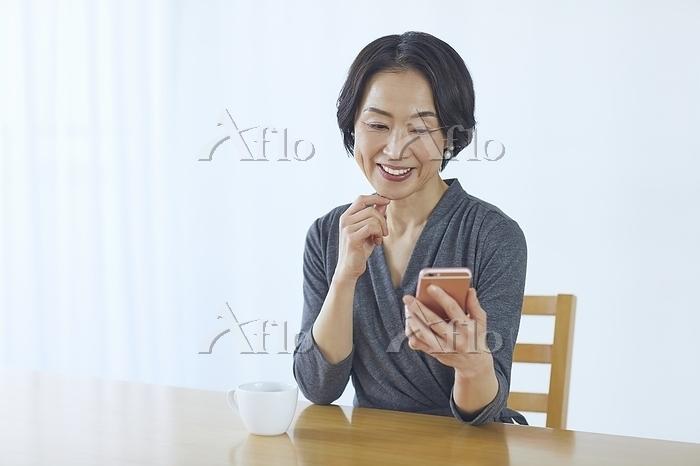 スマートフォンを見るシニアの日本人女性