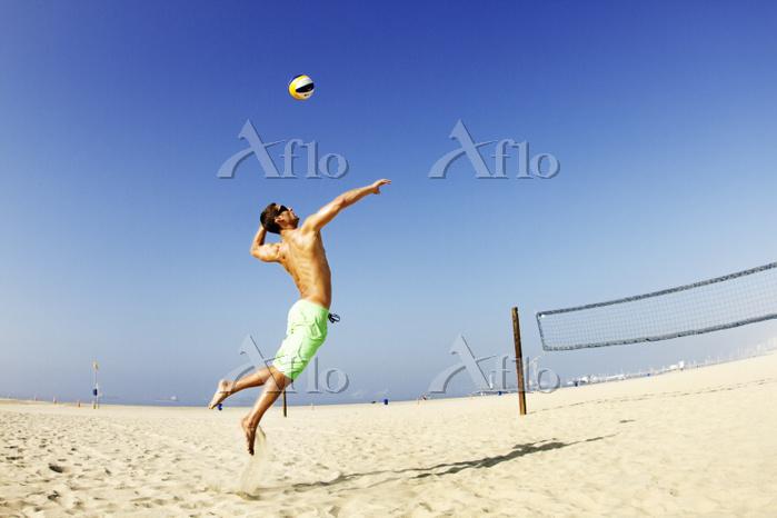 Man hitting ball at beach agai・・・