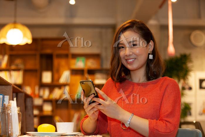 カフェでスマートフォンを持つ日本人女性