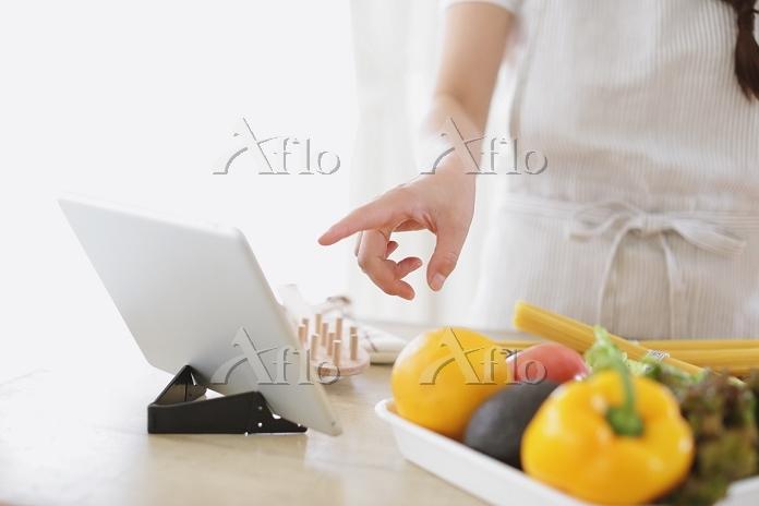 タブレットを見ながら調理する日本人女性