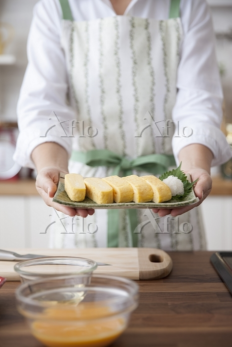 出汁巻き玉子を皿に載せて持つ女性