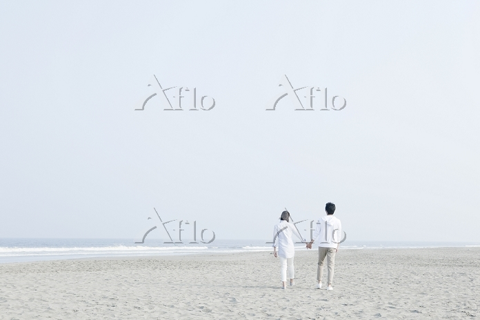 手を繋いで歩く海辺のカップルの後ろ姿
