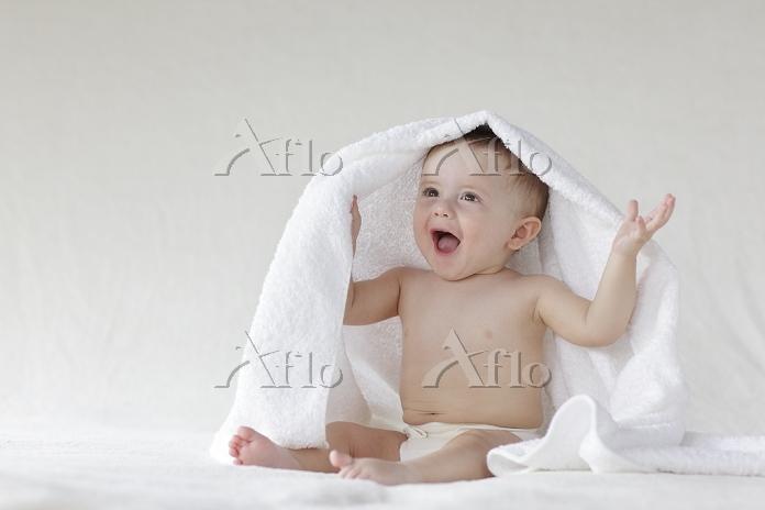 お座りをして頭にタオルをかけている赤ちゃん