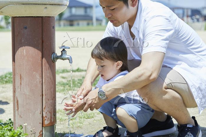 公園の水道で手を洗う男の子