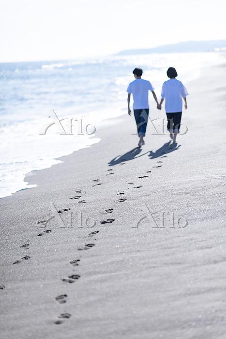 海辺で手をつなぐカップルの後ろ姿
